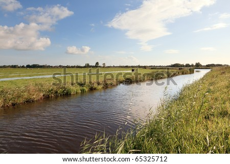 Landscape with canal under blue cloudy sky, the Netherlands - stock photo