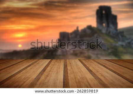 Landscape with castle ruins on hill and vibrant beautiful sunrise in distance with wooden planks floor - stock photo