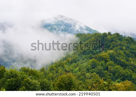 Landscape with clouds and mist over hills covered in forests in the Romanian mountains - stock photo