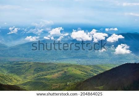 Landscape with clouds, mountains, blue sky and village. Carpathians, Ukraine.  - stock photo