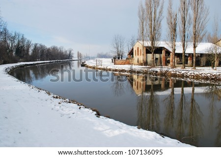 Landscape with country house covered of snow in winter and  trees reflecting on the river, Po valley, Italy - stock photo