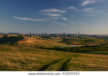 Landscape with country road to the valley in the spring foothills at green grass fields of Altai mountains at sunset under clear blue sky with white clouds, Siberia, Russia - stock photo