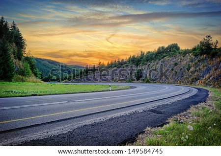 Landscape with curvy road at summer sunset  - stock photo