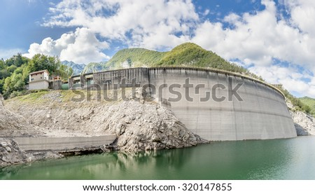 Landscape with dam for the production of electrical energy in the mountains - stock photo