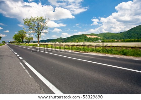 Landscape with empty road and trees under sky with clouds - stock photo