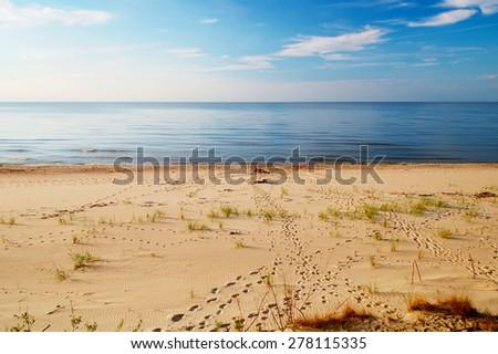 Landscape with footprints on a sunny, empty beach. Baltic sea shore, Pomerania, northern Poland. - stock photo