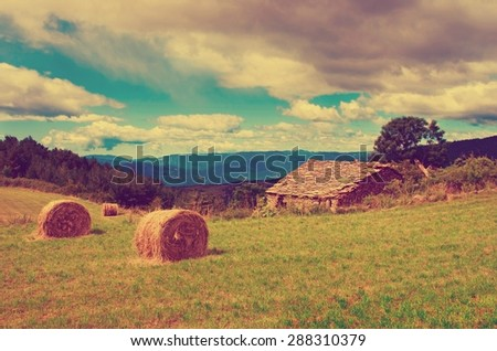 Landscape with harvested bales of straw in field and stone house, Spain - stock photo
