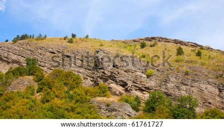Landscape with hills and forest under blue sky - stock photo