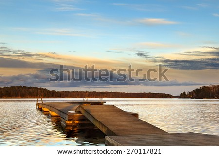 Landscape with jetty and water during dusk sunset - stock photo