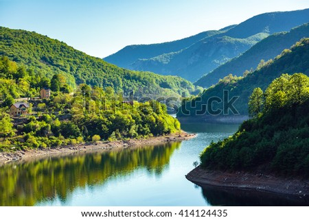 Landscape with lake between mountains covered in forest