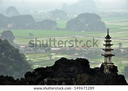 Landscape with limestone towers and rice fields in a rainy, cloudy day. Ninh Binh, Vietnam