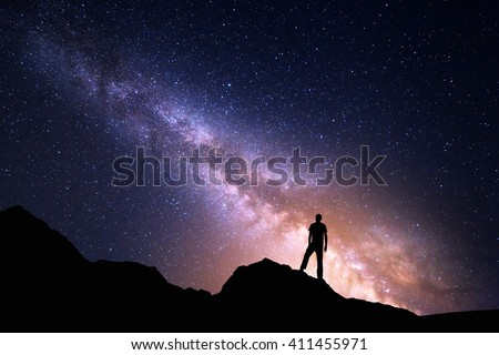 Landscape with Milky Way. Night sky with stars and silhouette of a happy man on the rock. Beautiful Universe. Space background - stock photo