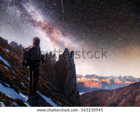 Landscape with milky way, Night sky with stars and silhouette of a standing photographer man on the mountain, Long exposure photograph, with grain