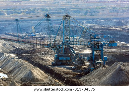 Landscape with mine machine on sunny day against blue sky - stock photo