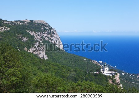 Landscape with mountains and church on a background of blue sea and sky - stock photo