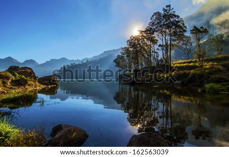 landscape with mountains trees and a lake in front segara danau anak lake, Mount Rinjani, Lombok, Indonesia - stock photo