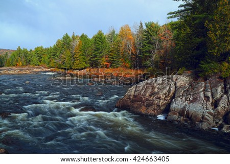 Landscape with mountains trees and a river in front.  Mountain river in fall forest with red yellow leafs and rocky shore. River in Quebec. Mountain river in autumn time. Stone River, Riverside rocks