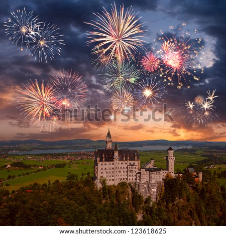 Landscape with Neuschwanstein castle and beautiful holiday fireworks in majestic sky - stock photo