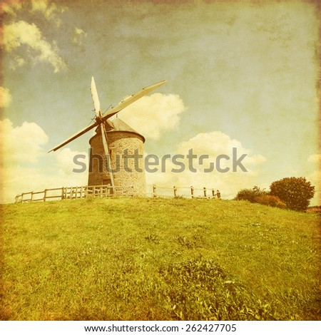 Landscape with old windmill in grunge and retro style.
