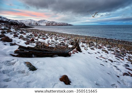 Landscape with old wooden boat lying on the beach at sunset,  Arctic, Arctic Ocean