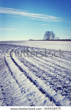 Landscape with plowed agricultural field in early winter - stock photo