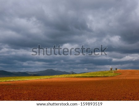 landscape with plowed field and sky with storm clouds