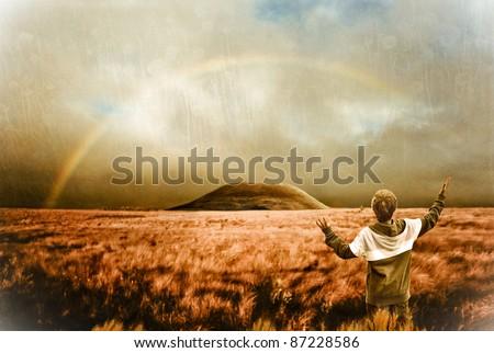 Landscape with rainbow and boy - spiritual scene, retro look image - stock photo