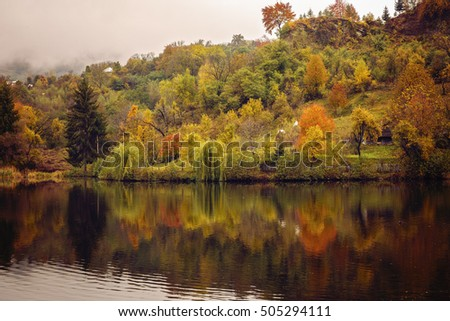 landscape with reflections of autumn colors on a lake