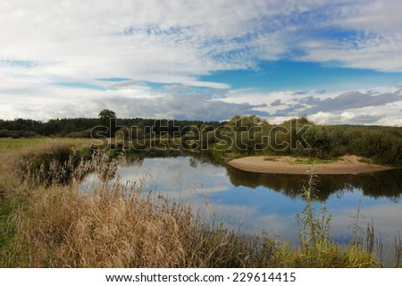 Landscape with river and clouds in early autumn - stock photo