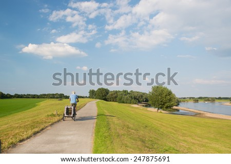 Landscape with river in Holland and man on bike with doggy car - stock photo