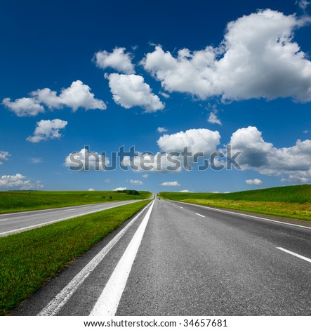 landscape with road and cloudy blue sky
