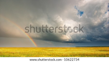 Landscape with storm clouds and rainbow - stock photo