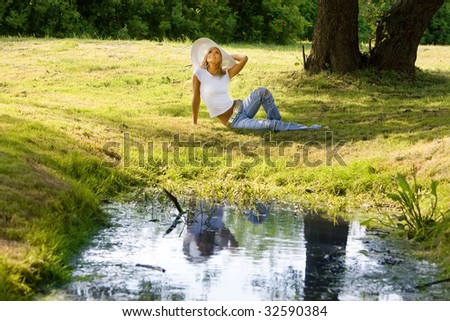 Landscape with the beautiful girl in a white hat on a glade - stock photo