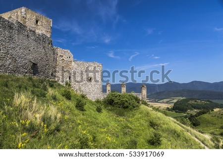 Landscape with the bright green vegetation, blue sky and a fragment of the ramparts of a medieval castle