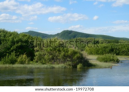 Landscape with the river and the blue sky - stock photo