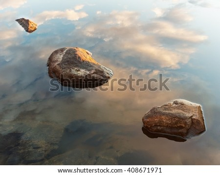 Landscape with three rocks in the water of a lake in Finland. Peaceful view with sky and cloud reflection in the clean and still water. - stock photo