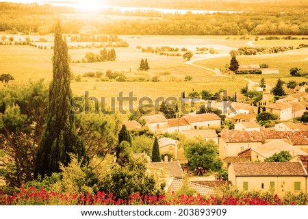 Landscape with vineyards and rural houses. A view from castle of Chateauneuf du Pape on the valley. Provence, France. Sunlight glow. Aged photo. Retro style postcard. - stock photo