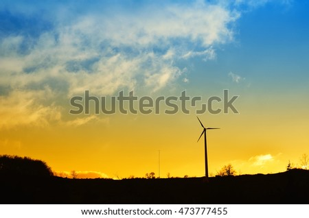 landscape with wind turbine and cloudy sky