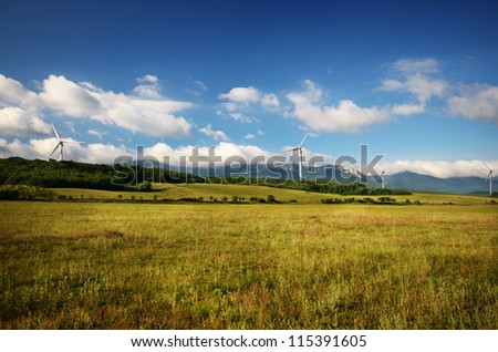 Landscape with wind turbines under blue cloudy sky, mountains at background - stock photo