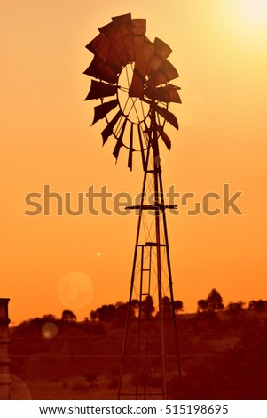 Landscape with windmill water pump on farm land at sunrise. Added filter and lens flare.