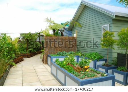 Landscaped back yard of a house with flowers and plants - stock photo
