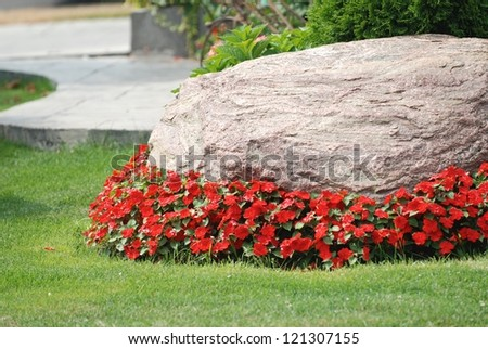 Landscaped flower garden with a rock and red flowers - stock photo