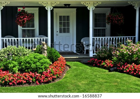 Landscaped front yard of a house with flowers and green lawn - stock photo