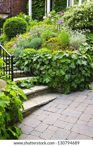 Landscaped garden path with natural stone steps and metal railing - stock photo