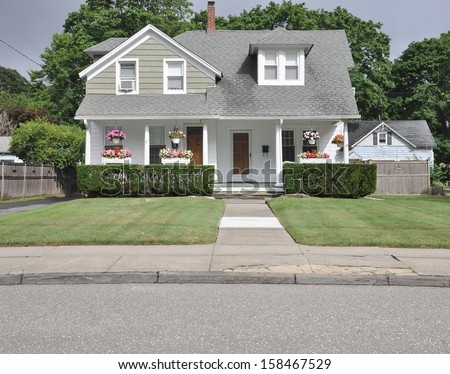 Landscaped Suburban Cape Cod Style Home Flowers Sidewalk Street Residential Neighborhood USA - stock photo