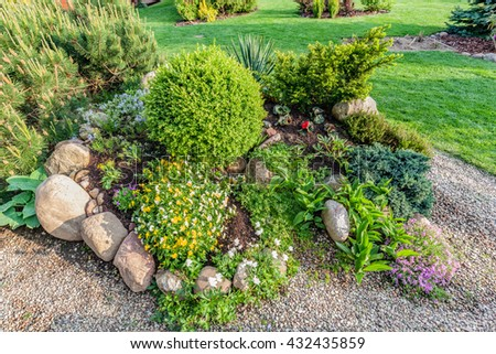 Landscaped Summer Garden With Green Plants, Rocks, Various Flowers In  Flowerbeds, Mown Grass