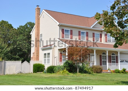 Landscaped Two Story Home with Siding in Suburban Residential Neighborhood on Blue Sky Sunny Day