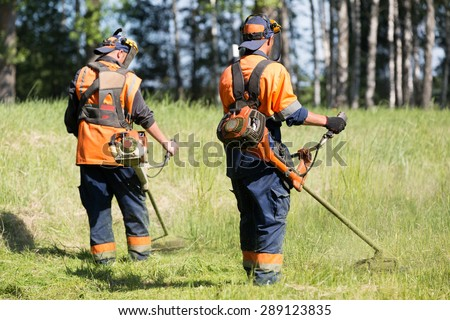 Landscapers men gardeners cutting grass with string lawn trimmers - stock photo