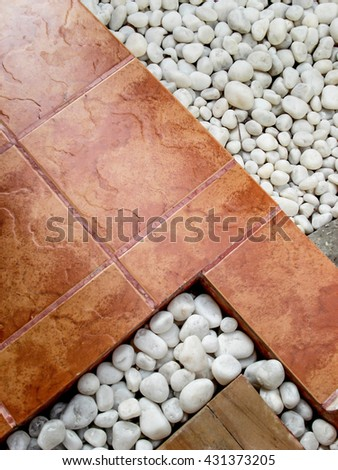 Landscaping combination of white pebbles and brown paving tiles. - stock photo