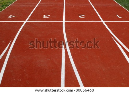 Lanes of a red race track with numbers for athletic venue - stock photo